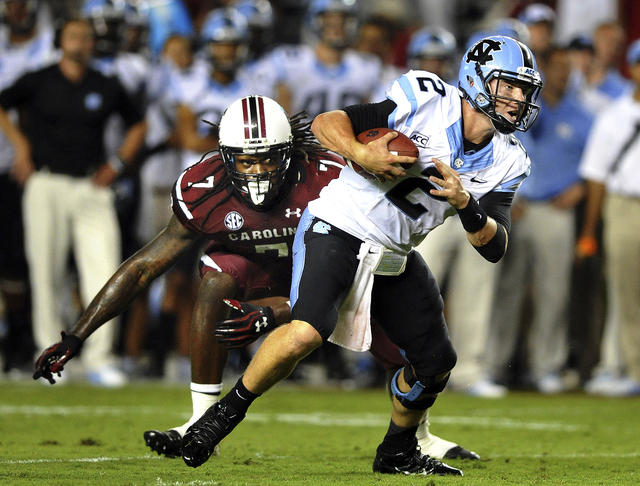 South Carolina defensive end Jadeveon Clowney (7) misses a sack of North Carolina quarterback Bryn Renner (2) during the second half of a game on Thursday in Columbia, S.C. A severe weather delay  ...