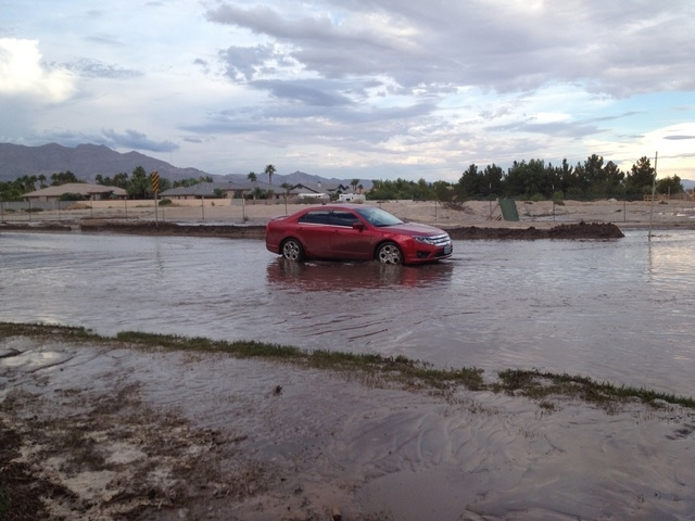 Keith Rogers/Las Vegas Review-Journal A red car gets caught in the dark water on Tenaya Way and Farm Road.