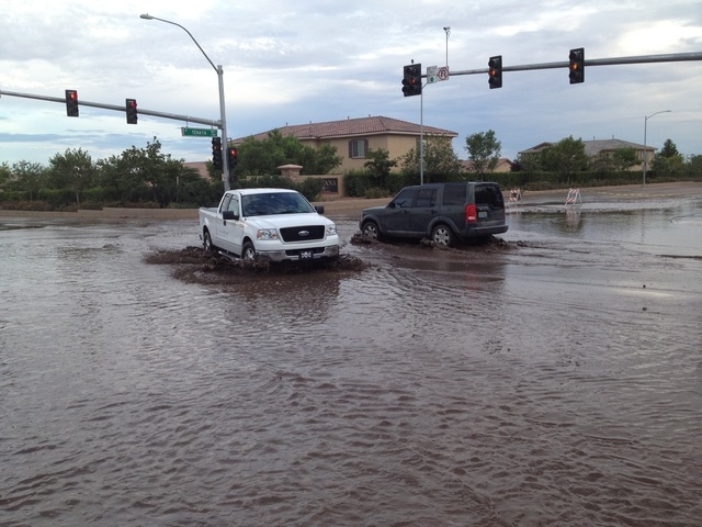 Keith Rogers/Las Vegas Review-Journal Two vehicles try to navigate through water on Tenaya Way and Farm Road.
