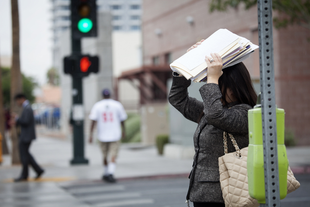 A woman shields herself from rain outside the Regional Justice Center in Las Vegas Monday, Aug. 26, 2013. A 50 percent chance of rain will hover over the valley throughout the week, according to t ...