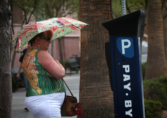 A woman named Claire who declined to give her last name uses an umbrella to shield herself from rain in downtown Las Vegas Monday, Aug. 26, 2013. A 50 percent chance of rain will hover over the va ...