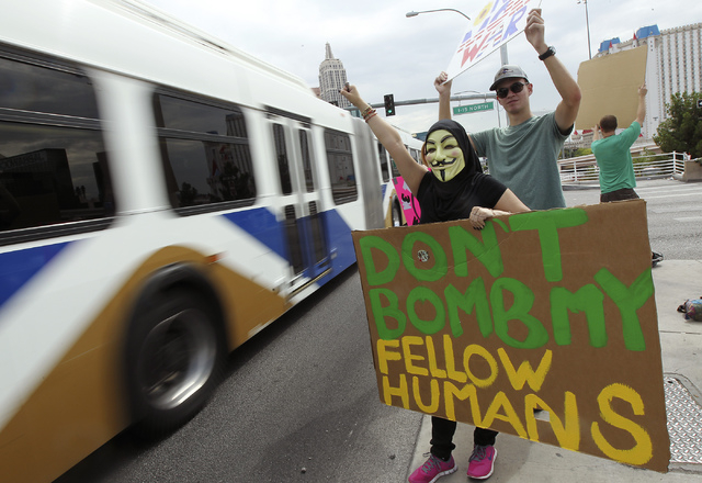Veronica Pacheco, in mask, holds a sign and petitions drivers as Las Vegas Activist Coalition members protest the possible U.S. intervention into Syria on the Tropicana overpass above I-15 in Las  ...