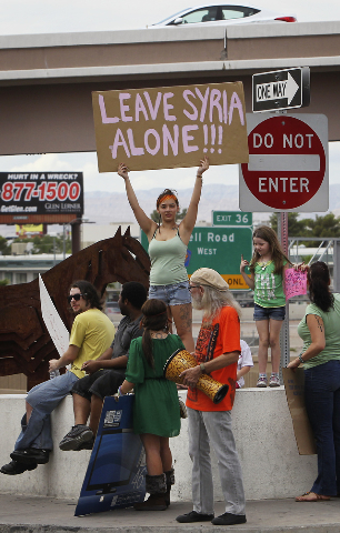 Morgan Pavlich, middle, holds a sign as Las Vegas Activist Coalition members protest the possible U.S. intervention into Syria on the Tropicana overpass above I-15 in Las Vegas on Aug. 31, 2013. ( ...