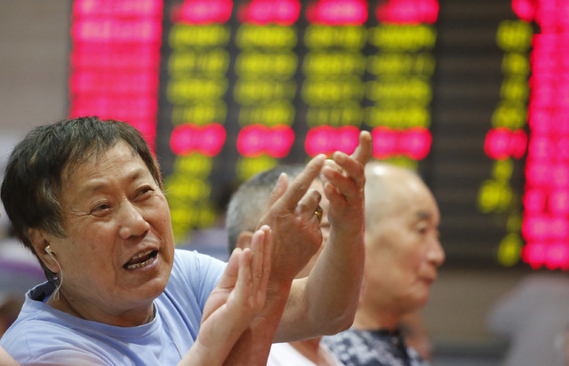 An investor gestures in front of the stock price monitor at a private securities company Monday Sept. 2, 2013 in Shanghai, China. Asian stock markets were mostly higher Monday after manufacturing  ...