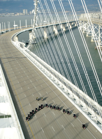 In this photo taken on Monday a phalanx of police officers cross the San Francisco-Oakland Bay Bridge after leading a procession marking the east span's opening, in San Francisco. (AP Photo/Bay Ar ...