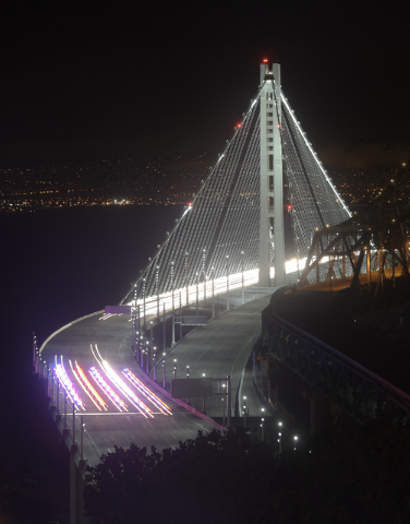 In this Monday photo taken in a long exposure and provided by the Bay Area Toll Authority, police vehicles open the San Francisco-Oakland Bay Bridge to traffic, in San Francisco. (AP Photo/Bay Are ...