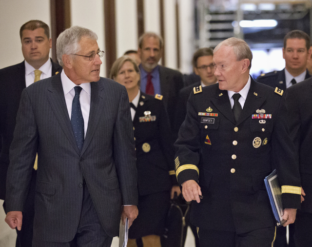 Defense Secretary Chuck Hagel, left, and Joint Chiefs Chairman Gen. Martin Dempsey, right, arrive for a closed-door intelligence briefing for members of the Senate Armed Services Committee, on Cap ...