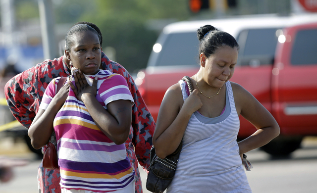Parents,  Eunice Pacheco, right, and LaKesia Brent, left, wait for news about their children outside Spring High School Wednesday, Sept. 4, 2013, in Spring, Texas.  A 16-year-old boy has been airl ...