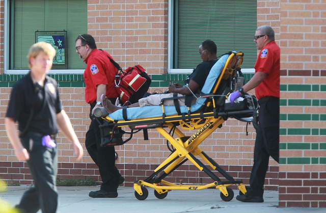 Emergency personnel remove a person from the school after at least one person was killed and others were injured during an altercation inside Spring High School Wednesday, Sept. 4, 2013, morning i ...