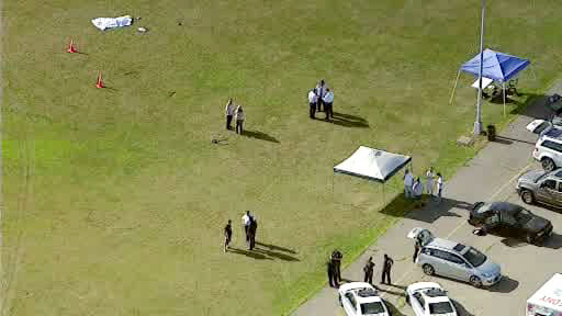 Investigators stand near a remote-controlled toy helicopter, center that apparently struck and killed a 19-year-old man, top left, Thursday, Sept. 5, 2013, at Calvert Vaux Park in the Brooklyn bor ...
