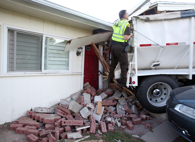 Utah Highway Patrol trooper Doug Whitlock inspect a trailer that crushed a vehicle before hitting a home, Thursday, Sept. 5, 2013, in Bountiful, Utah. Bountiful police Sgt. Andrew Bryson says the  ...