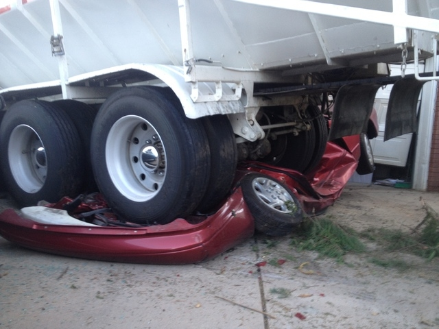 This photo released by the South Davis Metro Fire Agency shows a flattened car that was hit by a semitrailer on Thur. Sept. 5, 2013 in Bountiful, Utah. Authorities say nobody was injured when a se ...