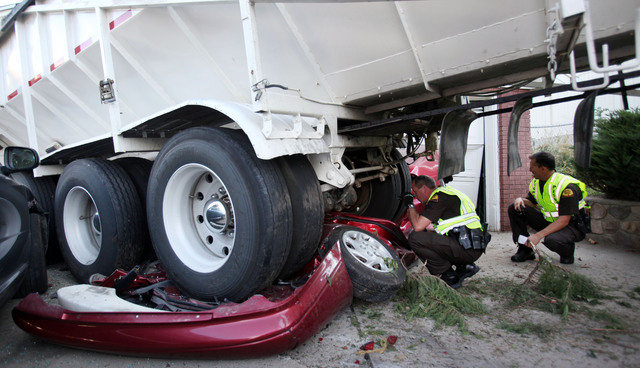 Utah Highway Patrol troopers Mark Johnson, left, and Doug Whitlock inspect a trailer that crushed a vehicle before hitting a home, Thursday, Sept. 5, 2013, in Bountiful, Utah. Bountiful police Sgt ...