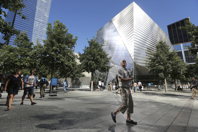 A visitor to the National September 11 Memorial and Museum takes in the sight as he walks past the museum, Friday in New York. Construction is racing ahead inside the museum as the 12th anniversar ...