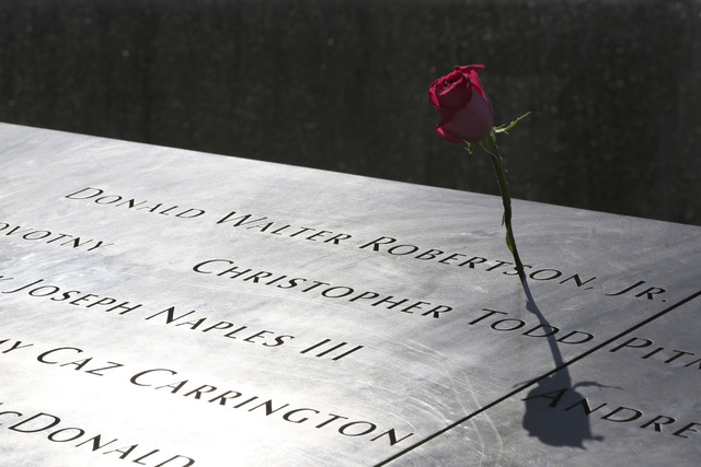 A rose is placed next to the name of a victim of the terrorist attacks on the World Trade Center at the North Pool of the National September 11 Memorial and Museum, Friday in New York. Constructio ...