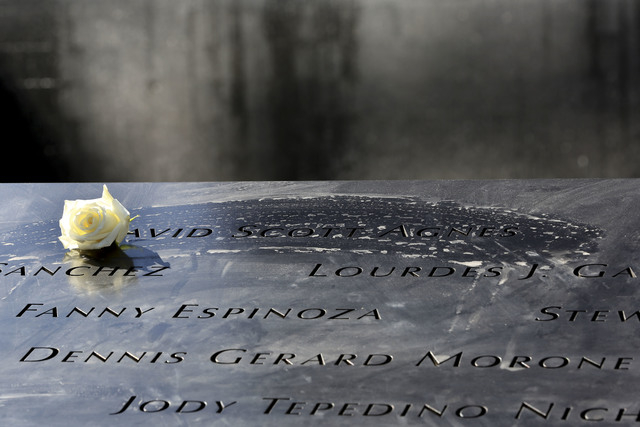 A rose is placed next to the name of a victim of the terrorist attacks on the World Trade Center at the North Pool of the National September 11 Memorial and Museum, Friday in New York.  Several mo ...