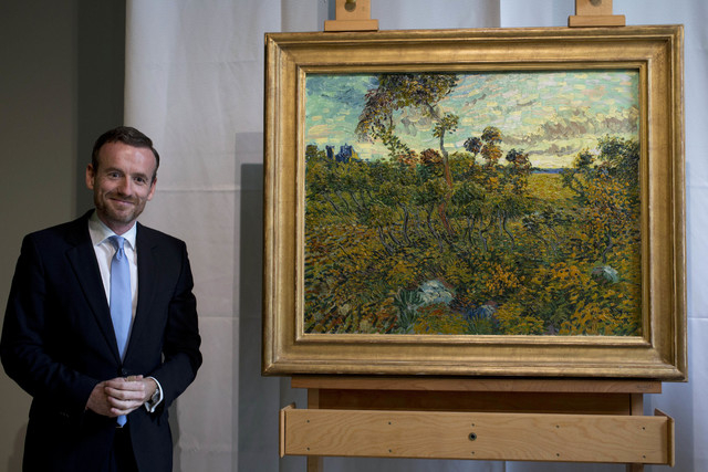 "Van Gogh Museum director Axel Ruger, left, poses next to ""Sunset at Montmajour"" after unveiling the painting by Dutch painter Vincent van Gogh during a press conference at the museum in  ..."