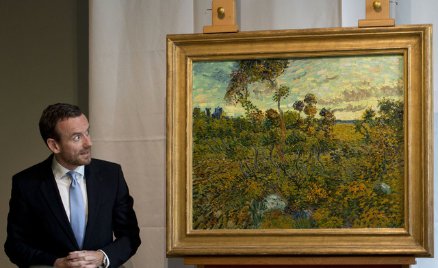 "Van Gogh Museum director Axel Ruger, left, looks at ""Sunset at Montmajour"" after unveiling the painting by Dutch painter Voncent van Gogh during a press conference at the museum in Amste ..."