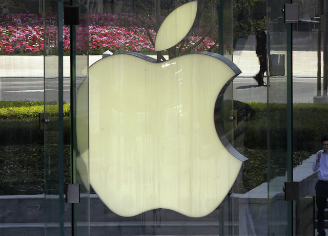 In this April 2, 2013, file photo, a man smokes near the logo of Apple in Shanghai. Apple is expected to unveil its latest version of the iPhone on Tuesday, Sept. 10, 2013. (AP Photo/Eugene Hoshik ...