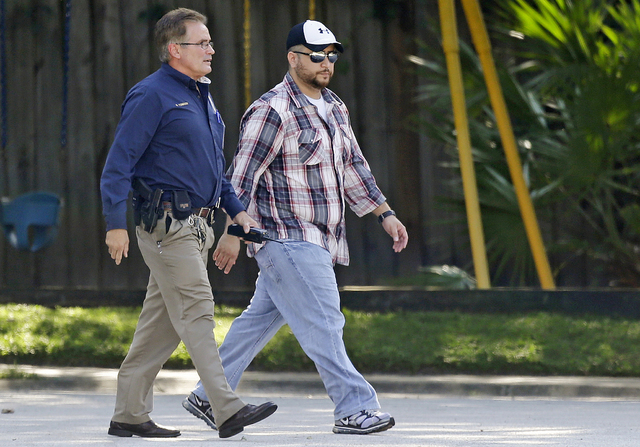 George Zimmerman, right, is escorted to a home by a Lake Mary police officer, Monday in Lake Mary, Fla., after a domestic incident in the neighborhood where Zimmerman and his wife Shellie had live ...