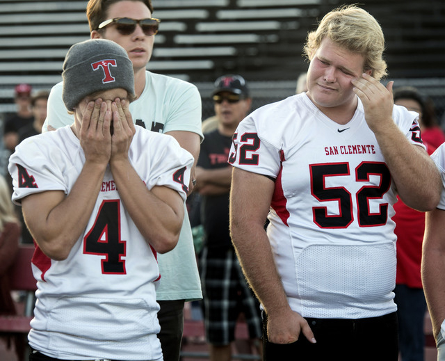 Torrey Larson, 18, left, and Troy Fullerton, 17, are overcome with emotion at a vigil for former San Clemente High teammate and UCLA wide receiver Nick Pasquale, 20, who died early Sunday after he ...