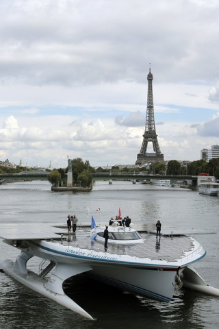 The Turanor PlanetSolar, the world's largest solar boat, travels on the Seine river as the Eiffel Tower is seen in background, in Paris, Tuesday. The  PlanetSolar with its 537 square meters of pho ...