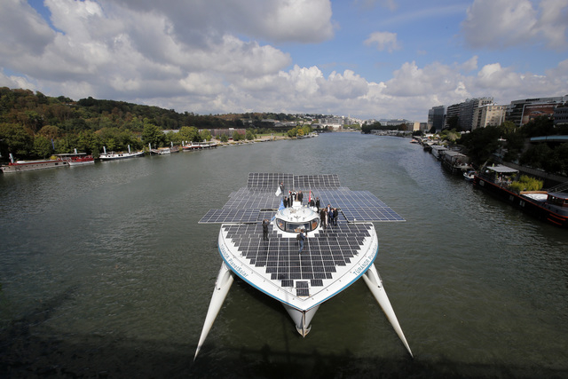 The Turanor PlanetSolar, the world's largest solar boat, travels on the Seine river in Sevres, outside Paris, Tuesday. The PlanetSolar with its 537 square meters of photovoltaic panels powering 6  ...