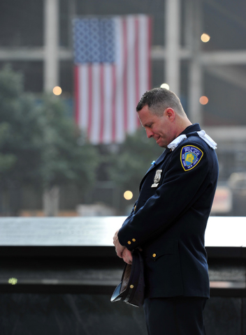 Daniel Henry, a Port Authority of New York/New Jersey police officer, pauses during a moment of silence at 9:01 a.m. at the south reflecting pool at the 9/11 Memorial on Wednesday, Sept. 11, 2013, ...