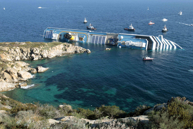 In this Jan. 14, 2012 file photo the luxury cruise ship Costa Concordia leans on its side after running aground in the tiny Tuscan island of Giglio, Italy. Italian authorities say the bold operati ...