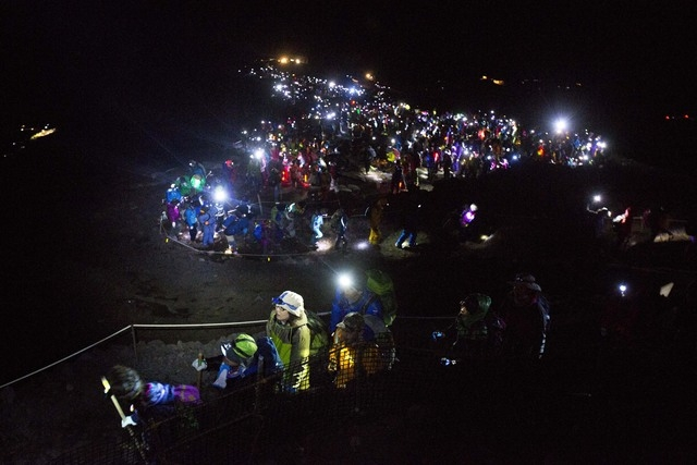 In this Sunday, Aug. 11 photo, thousands of hikers, with headlamps and flashlights lighting their way, climb to the summit of Mount Fuji in Japan before dawn. (AP Photo/David Guttenfelder)