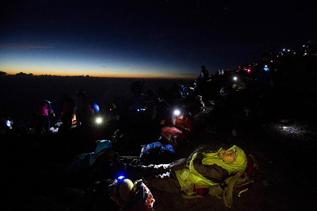 In this Aug. 11 photo, thousands of hikers wait for the sun to rise on the summit of Mount Fuji before dawn. The recent recognition of the 3,776-meter (12,388-foot) peak as a UNESCO World Heritage ...