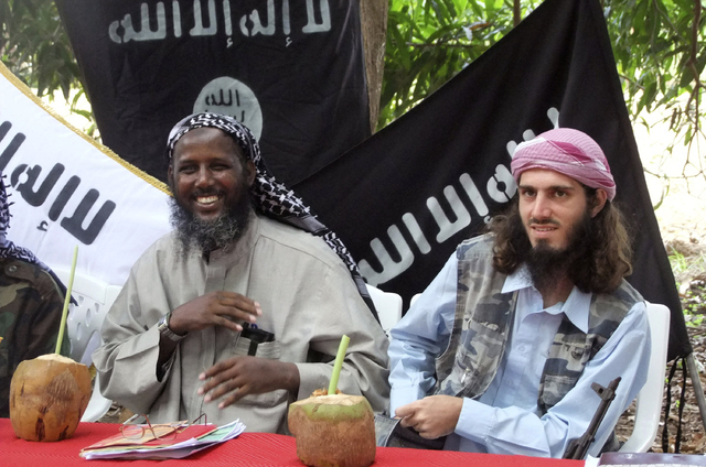 "American-born Islamist militant Omar Hammami, right, and deputy leader of al-Shabab Sheik Mukhtar Abu Mansur Robow sit under a banner which reads ""Allah is Great"" during a news conference of the m ..."