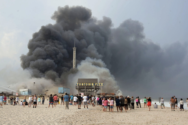 Onlookers watch from the shore as black smoke rises from a fire on the Seaside Heights, N.J. boardwalk Thursday, Sept. 12, 2013. The fire started in the vicinity of an ice cream shop and burned se ...