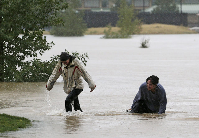 A couple plays in flood water at Utah Park in Aurora, Colo., on Thursday, Sept. 12, 2013. The park was under water due to flooding. Flash flooding in Colorado has cut off access to towns, closed t ...