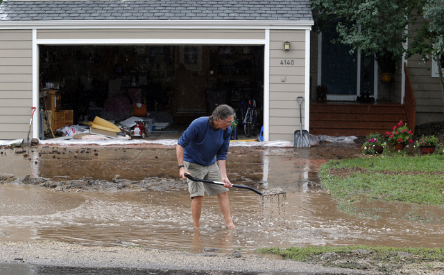 Brian Flynn, of Oregon, clears a drain in front of his sister's home in Boulder, Colo., on Thursday, Sept. 12, 2013. Flash flooding in Colorado has cut off access to towns, closed the University o ...