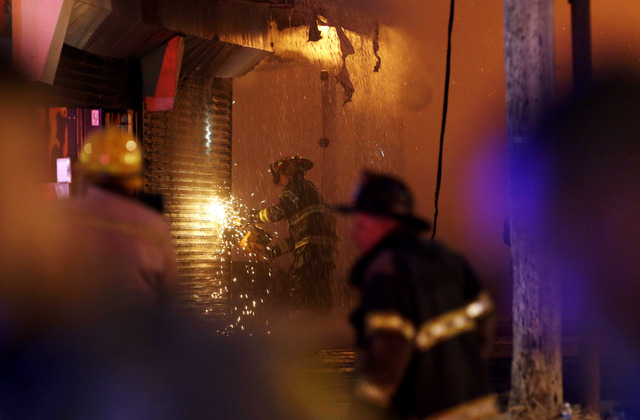 A firefighter saws through a metal wall on a building while battling a fire at the Seaside Park boardwalk on Thursday in Seaside Park, N.J. The fire began in a frozen custard stand on the Seaside  ...