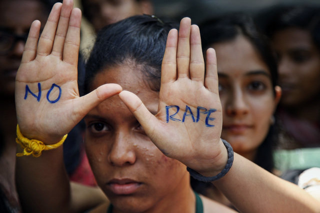 "An Indian student displays ""NO RAPE"" message painted on her hands during a demonstration to demand death sentence for four men convicted of rape and murder of a student on a moving bus i ..."