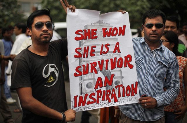 Indians hold a placard outside a court after a judge sentenced to death four men for the December rape and murder of a student on a moving New Delhi bus, in New Delhi, India, Friday, Sept. 13, 201 ...