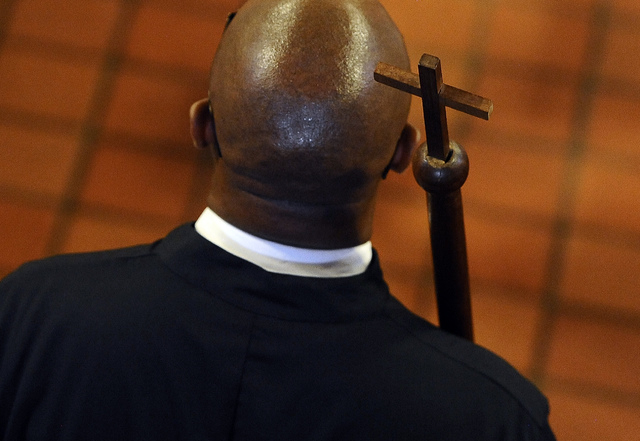 Steven R Mullins carries a cross at a memorial service for an enslaved man known as Mr. Fortune at St. John's Episcopal Church in Waterbury, Conn., Thursday, Sept. 12, 2013.  Mr. Fortune is being  ...