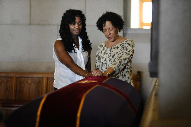 Tamara Lanier of Norwich, Conn., left, and Gabrielle Foreman of Delaware, pray over a casket with the remains of an enslaved man known as Mr. Fortune at the Capitol in Hartford, Conn., Thursday, S ...