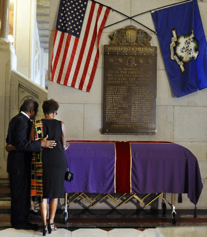 Caleb Pilgrim, left, and Marie Baskerville pray over a casket with the remains of an enslaved man known as Mr. Fortune at the state Capitol in Hartford, Conn., Thursday, Sept. 12, 2013.  Mr. Fortu ...