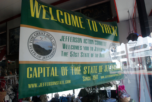 In this Sept. 6, 2013 photo, a banner welcoming visitors to the State of Jefferson hangs in the window of a downtown business in Yreka, Calif. Movements to form a new state with counties from Nort ...