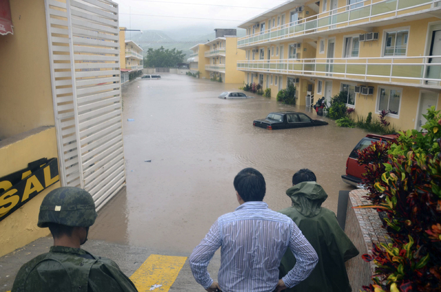 Army soldiers and a civilian look out into a flooded street caused by Tropical Storm Manuel in the city of Chilpancingo, Mexico, Sunday Sept. 15, 2013. In the southern Pacific Coast state of Guerr ...