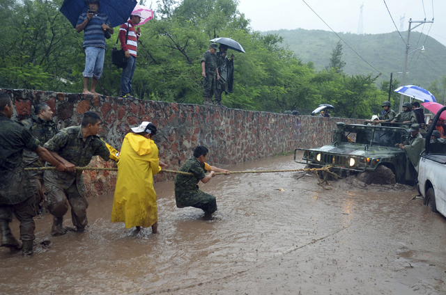 Army soldiers work to try to get their vehicle out of a flooded portion of a road caused by Tropical Storm Manuel in the city of Chilpancingo, Mexico, Sunday Sept. 15, 2013. In the southern Pacifi ...
