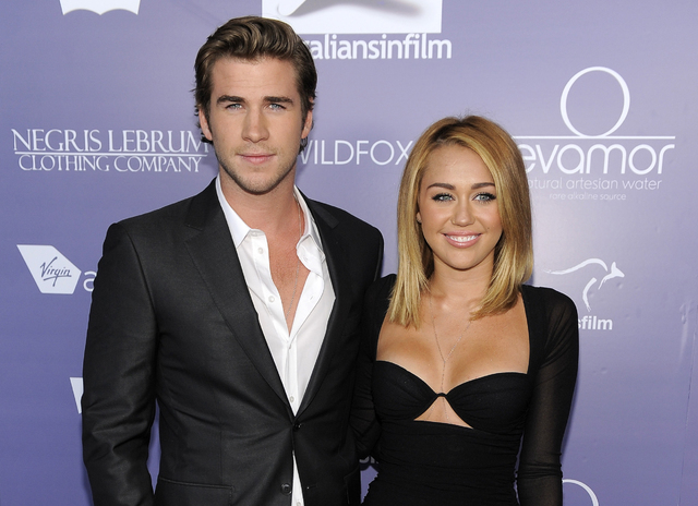 FILE - In this June 27, 2012 file photo, actor Liam Hemsworth, left, an honoree at the Australians in Film 8th Annual Breakthrough Awards, poses with his fiance Miley Cyrus on the red carpet in Lo ...