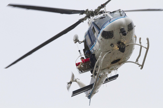 A U.S. Park Police helicopter removes a man in a basket from the Washington Navy Yard Monday, Sept. 16, 2013.  Earlier in the day, the U.S. Navy said it was searching for an active shooter at the  ...