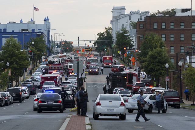 Police work the scene on M Street, SE in Washington, where a gunman was reported at the Washington Navy Yard in Washington, on Monday. The U.S. Navy says one person is injured after a shooting at  ...
