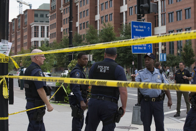 Police work the scene on M Street, SE in Washington near the Washington Navy Yard on Monday. The U.S. Navy says one person is injured after a shooting at a Navy building in Washington. Police and  ...