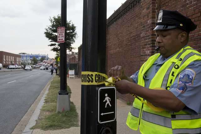 Police work the scene on M Street S.E. in Washington, where a gunman was reported in a military building at the Washington Navy Yard Monday, Sept. 16, 2013. Shots have been fired and employees dir ...