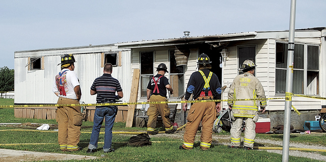 Fire officials stand outside a mobile home that caught fire and killed a man and five children in Tiffin, Ohio, Sunday, Sept. 15, 2013, according to police. Fire crews pulled the man and the child ...